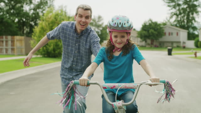 Medium slow motion tracking shot of father teaching daughter to ride bicycle / Provo, Utah, United States