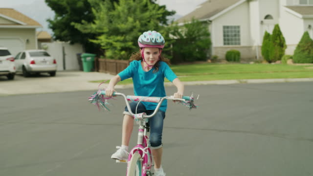 Medium slow motion tracking shot of girl riding bicycle in street / Provo, Utah, United States