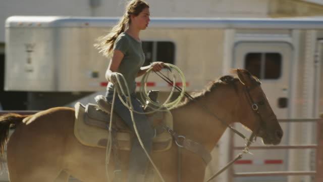 Medium slow motion tracking shot of girl riding horse holding lasso / Lehi, Utah, United States