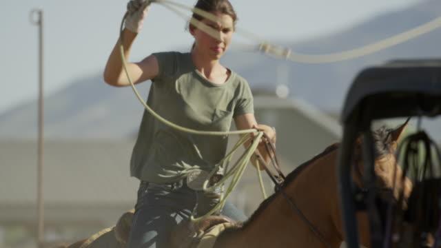 Medium slow motion tracking shot of girl riding horse throwing lasso / Lehi, Utah, United States