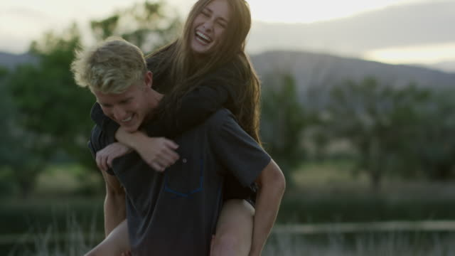 Medium slow motion tracking shot of man carrying girlfriend piggyback / Mona, Utah, United States