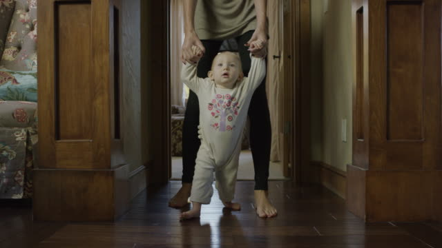 Medium slow motion tracking shot of mother helping baby daughter walk / Cedar Hills, Utah, United States