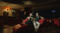 Medium, slow motion wide shot, of couple drinking and kissing in lounge / Arenal, La Fortuna, Costa Rica