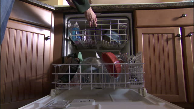 Medium static , A homeowner closes a dish washer full of dirty dishes. /