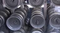 Medium static - A machine lifts metal wheels out of a liquid bath