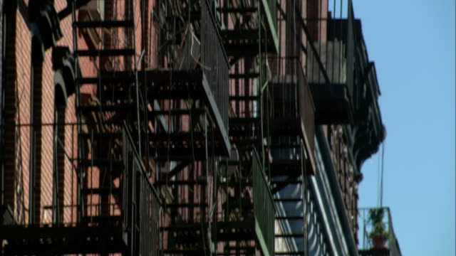 Medium tilt-down - Advertising signage hangs between fire escapes in lower Manhattan. / New York City, New York, USA