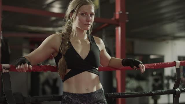 Medium tilting shot of female boxer leaning on ropes / Lehi, Utah, United States