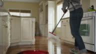 'Medium tracking panning shot of woman mopping kitchen floor / Cedar Hills, Utah, United States'