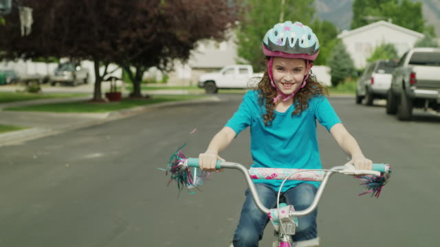 Medium tracking shot of girl riding bicycle in street / Provo, Utah, United States