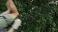 Medium tracking shot of man swinging on zipline in rain forest / Quepos, Puntarenas, Costa Rica