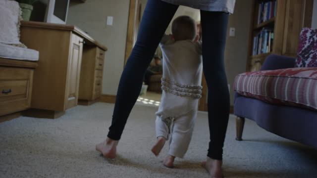 Medium tracking shot of mother helping baby daughter walk / Cedar Hills, Utah, United States