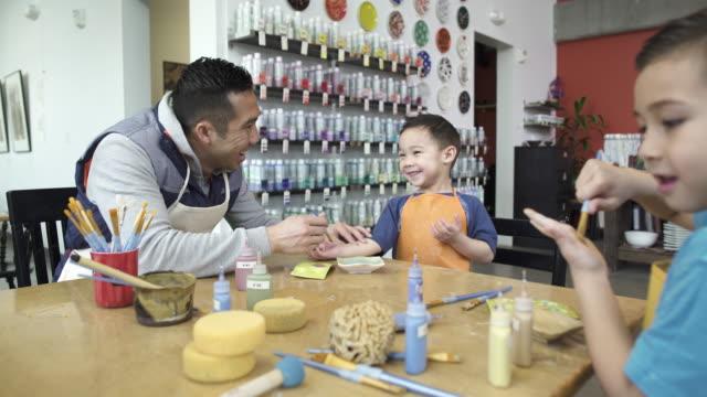 Medium wide shot of a family in a ceramic studio