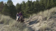 Medium wide shot of two girls riding on horses