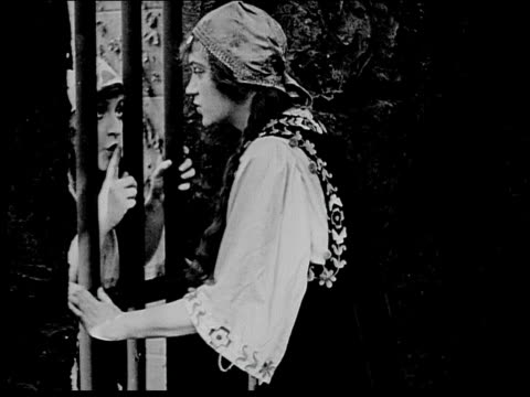 1916 B/W Medium woman talking to female prisoner through bars and helping to plan escape