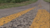 Medium zoom-out - A close-up view shows yellow painted lines and crumbling asphalt on a rural two-lane road. / USA