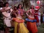 Medium-shot of hula dancers performing at a luau.
