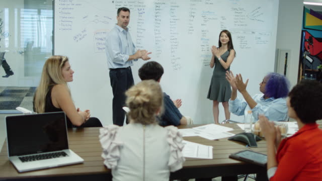 Meeting Attendees in Creative Office Space Applauding