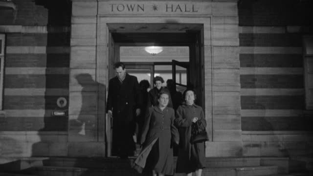WS Meeting attendees walking out of town hall building at night / United Kingdom