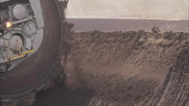 A Mega Machine digger carves up a hill.