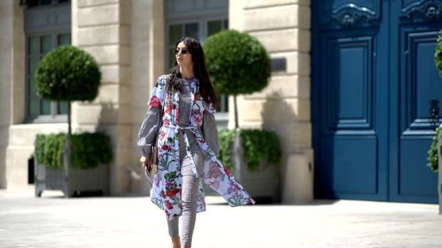 Melanie Darmon wears sunglasses a flower print dress a checkered black and white outfit and silver shoes outside Alexis Mabille during Paris Fashion...