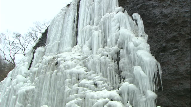 Melting ice creates a stream at the base of a frozen waterfall in the Unryu Valley in Oku-nikko, Japan.