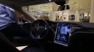 A member of the Moscow Tesla Club demonstrates the operation of the touchsensitive digital control screen inside a Tesla S P85D electric vehicle...