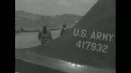 Member of US Air Force walks out of building on airfield in Korea carrying metal case / CU metal case with words on side saying 'Camera Aircraft Type...