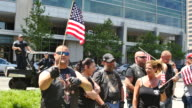 Members of an antiIslamic biker group wave flags while one saying he's 'an American' threatens to assault a counter protester during the 'antiSharia'...