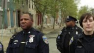Members of Baltimore Police Department stand guard outside the Western District Police Station as protesters gather prior to a march in honor of...