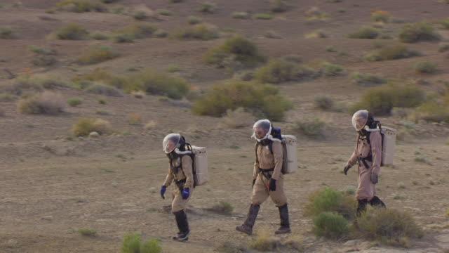 CU AERIAL DS Members of EVA team walking along rim in terrain resembling Mars at Mars desert research station in san Rafael desert / Utah, United States