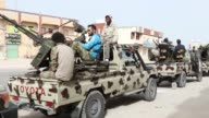 Members of proGeneral National Congress forces stand on machine gun mounted pickup trucks during a military parade following battle against the Daesh...