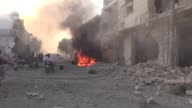 Members of Syrian civil defense team try to extinguish fire as they carry out search and rescue operations after warcrafts of Syrian Army bombed a...
