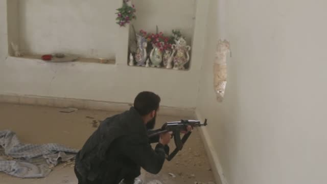 Members of Syrian opposition Shuhada alIslam Brigade clash with Syrian regime forces after a Syrian regime helicopter dropped multiple bombs on the...
