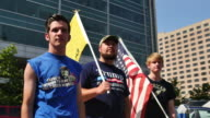 Members of the altright stand together with the American flag a Don't Tread on Me Flag and wearing a Trump shirt while watching speakers from their...