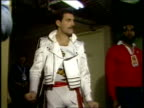 Members of the band Queen leaving dressing room and walking down hallway accompanied by a group of people / Freddie Mercury Fred Mandel Brian May...