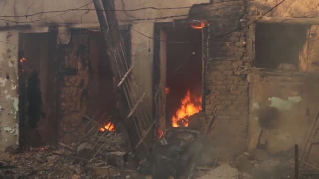 Members of the Syrian Civil Defence known as the white helmets attempted to extinguish flames following an air raid Wednesday on the rebel held town...