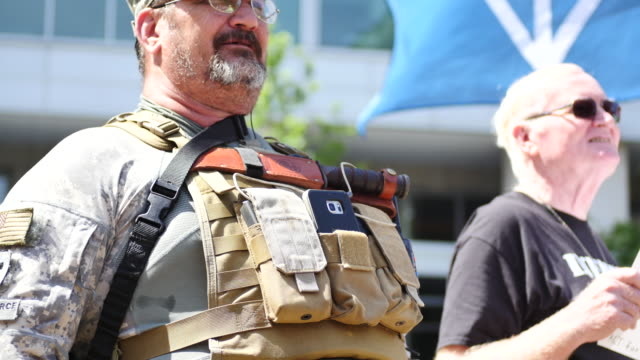 Members of the ThreePercenters militia armed with AR15 military rifles with extra clips of ammo stand next to altright protesters during the...