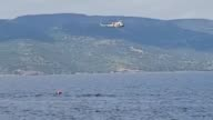 Members of Turkish and Greek Coast Guards search for survivors after a boat carrying them from Turkey to Lesbos sank in the Aegean Sea on April 24...