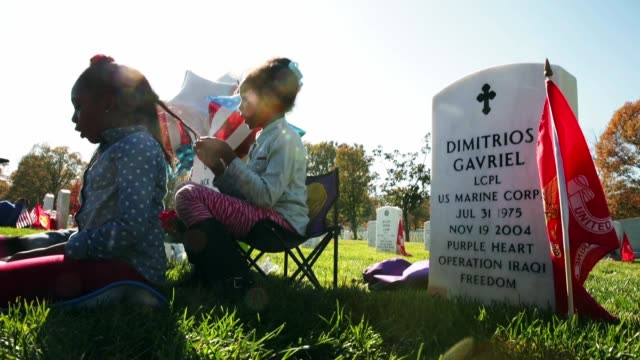 Members of US Army Sgt Jack Bryant's family including nieces Jayla Robinson 7 and Jayda Souza 9 spend time at his grave on Veterans Day in Section 60...