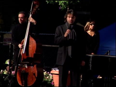 WTC Memorial Ground Zero NYC October 28 2001 VS Italian tenor Andrea Bocelli performs Ave Maria onstage ZO crowd Musicians policeman in background...