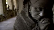 A memorial statue depicts an elderly woman crying and praying mournfully. Available in HD.