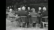 Men and a priest seated at outdoor table / Note exact day not known