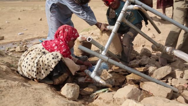 Men and children from a village in near Najran Saudi Arabia on June 8 2015 Shots of Wide shots of children from a local village playing with a water...