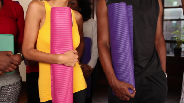 Men and women in yoga attire holding rolled up yoga mats