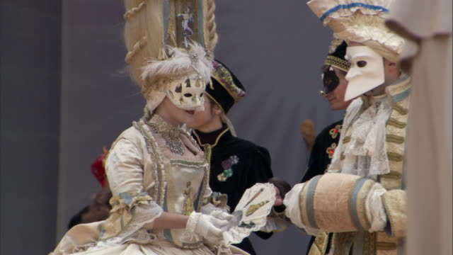 MS PAN men and women walking down stage in Piazza San Marco dressed in lavish 18th century style costume for Carnevale in Venice / Venice, Veneto, Italy