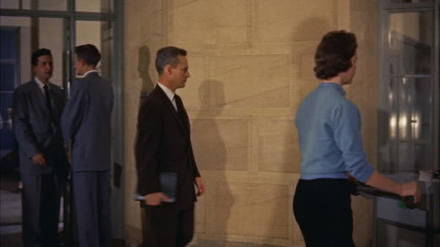 WS PAN Men and women walking in hallway of fbi assembly / Washington D.C., United States