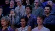 Men and women watching horror movie in theatre / cringing and laughing