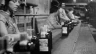 men and women working in a whiskey factory after prohibition repeal / depicts process of creating and bottling the alcohol / alcohol bottles on...