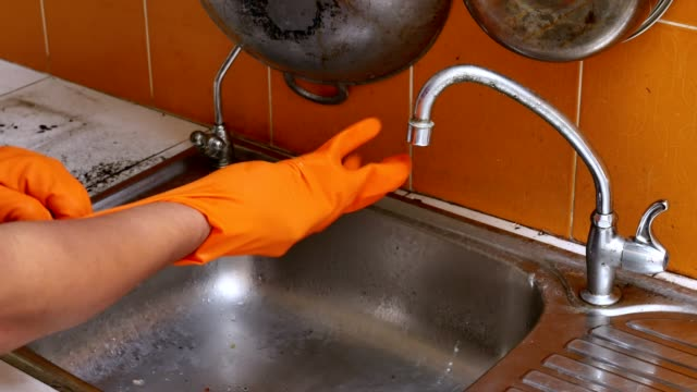 Men are cleaning the sink.
