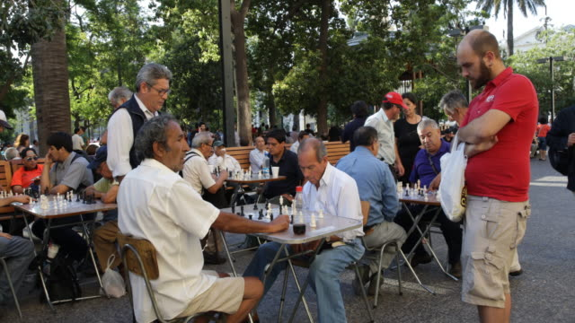 Men are playing chess at the Plaza de Armas square and other people are resting on benches Plaza de Armas is the main square of Santiago de Chile and...